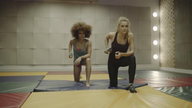 vídeos y material grabado en eventos de stock de young women lifting weights in gym - sólo mujeres jóvenes