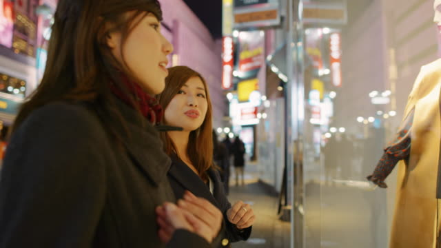 stockvideo's en b-roll-footage met ms young women look at a shop window / tokyo, japan - etalage