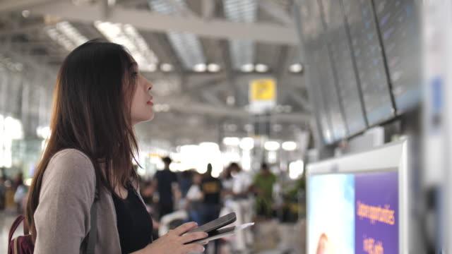Jonge vrouwen die kijken naar de luchthaven van aankomst vertrek bestuur