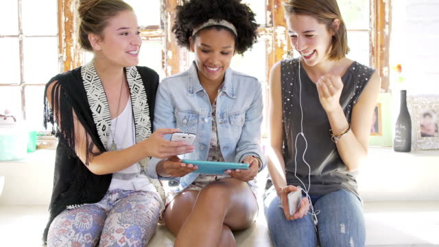 Young women looking at smartphones and tablet and laughing