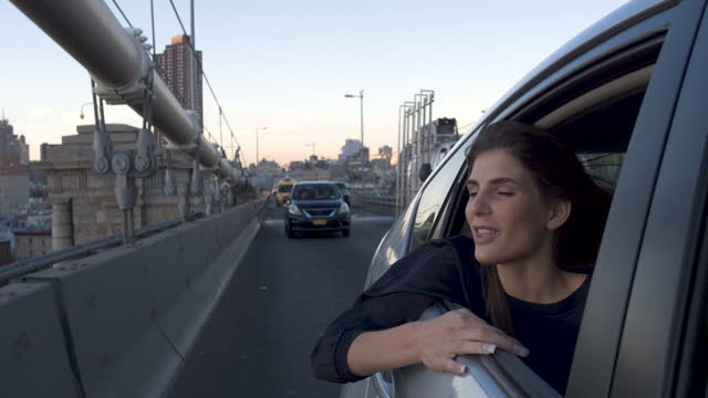 vídeos de stock e filmes b-roll de young women looking out of car window, sunset - apontar sinal manual