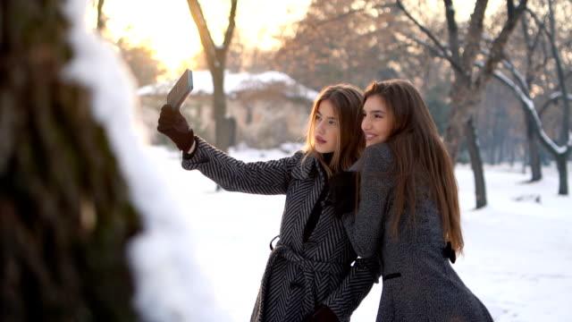 unga kvinnor som gör selfie i snö - rynka ihop ansiktet bildbanksvideor och videomaterial från bakom kulisserna