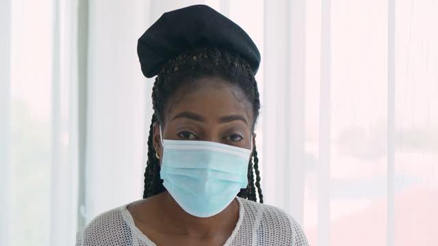 vidéos et rushes de les jeunes femmes de l'ethnie africaine noire âgées de 30 ans enlève le masque médical et souriant regardant la caméra de confiance pour empêcher des épidémies de coronavirus ou de covid-19.masques et revêtements faciaux (non caucasiens) concept - new age concept