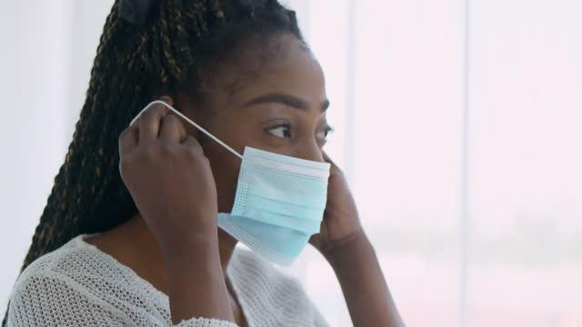 vidéos et rushes de jeunes femmes d'origine ethnique africaine noire âgées de 30 ans portant un masque protecteur de confiance pour prévenir les épidémies de coronavirus ou covid-19 tout en regardant par les fenêtres à la maison. masques et revêtements (non caucasie - new age concept