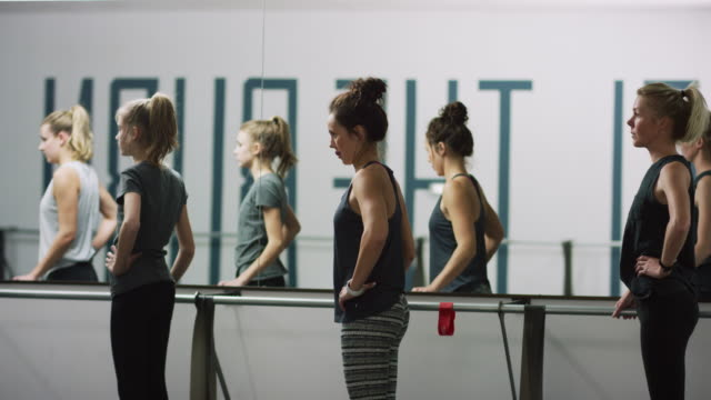 young women of mixed ages stand at a ballet barre on their tiptoes in an exercise studio - barre stock videos & royalty-free footage