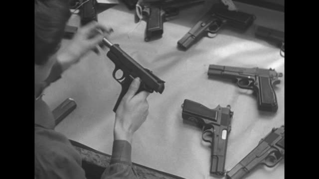 vs young women on assembly line put together parts for small browning 9mm automatic pistols / cu canadian seal on gun / chinese major y l chen puts... - crate stock videos & royalty-free footage