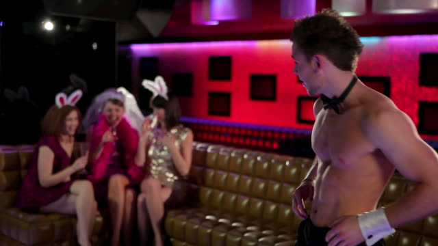 vidéos et rushes de young women on hen night with male stripper pulling off trousers - ballotter