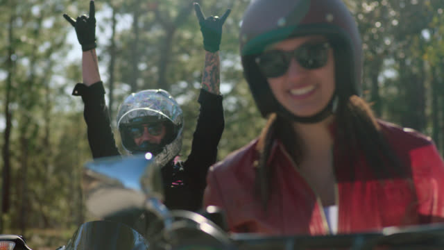 slo mo. young women on motorcycles laugh and throw hands in the air with rock and roll gestures. - バイカー点の映像素材/bロール