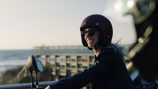 ms slo mo. young women on motorcycles laugh together overlooking the ocean. - ヘルメット点の映像素材/bロール