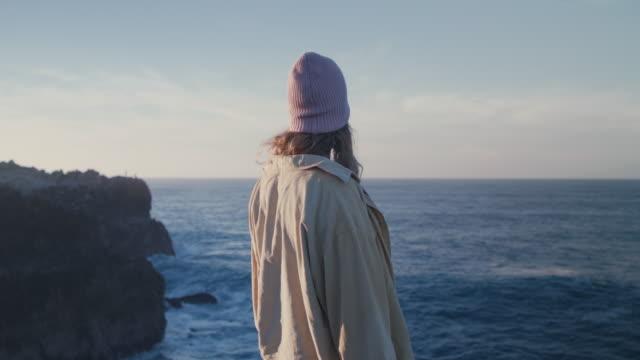 vídeos y material grabado en eventos de stock de young women on sea cliffs looking out at waves - brazos estirados