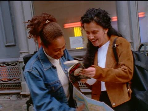pan 2 young women (1 black, 1 iranian) on street corner looking at map + laughing / nyc - 1990~1999年点の映像素材/bロール