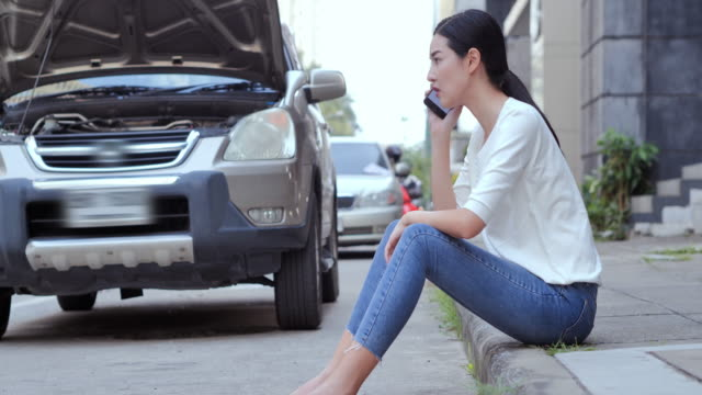young women opened the hood car on the side see engines and using mobile phone while looking at broken down car on street.technology,insurance,people,transportation concept. - roadside stock videos & royalty-free footage