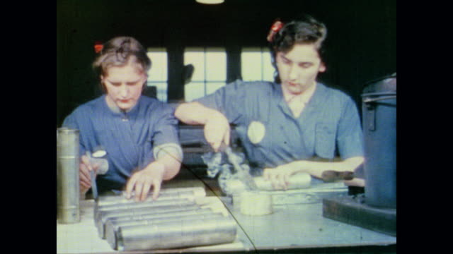 young women operate machinery in sheet metal shop - 1942年点の映像素材/bロール