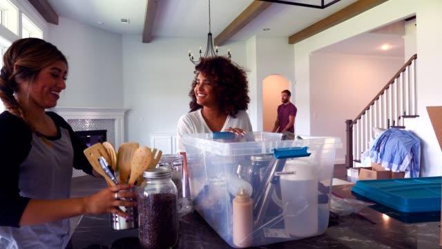 若い女性は、新しい家でキッチンを整理します - プラスチック容器点の映像素材/bロール