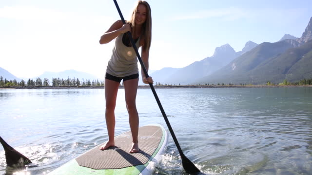 Young women paddleboard across mountain lake, standing up