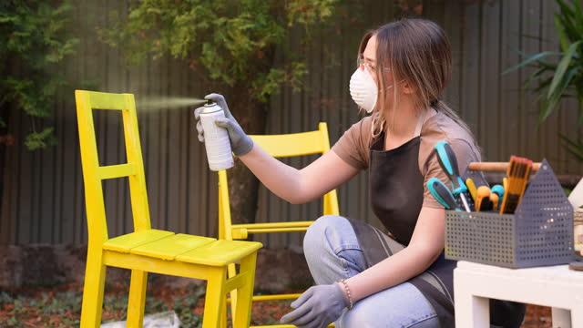 giovani donne che dipingeno mobili nel cortile di casa - bricolage video stock e b–roll
