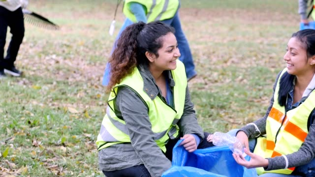 young women participate in community cleanup day in their neighborhood - servizio sociale video stock e b–roll