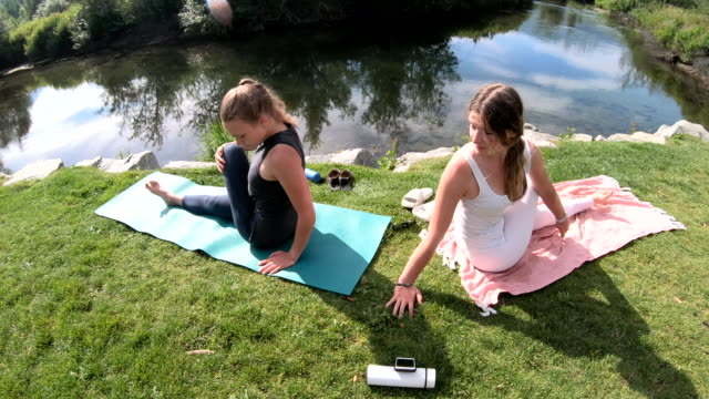 young women perform yoga moves together along a mountain river in the morning - slipper stock videos & royalty-free footage