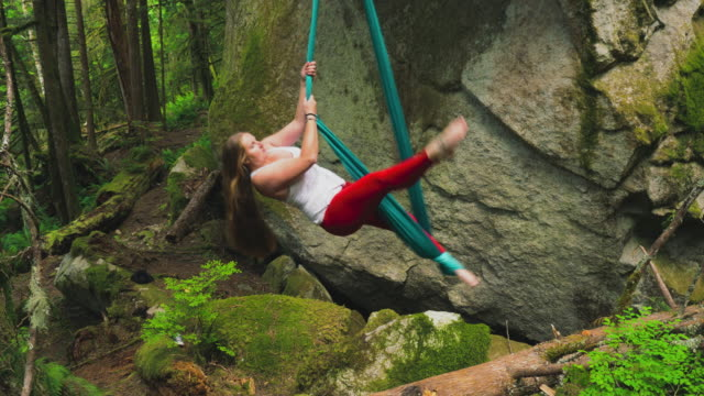 vidéos et rushes de young women performs on a aerial hammock in a lush forest - boulder rock