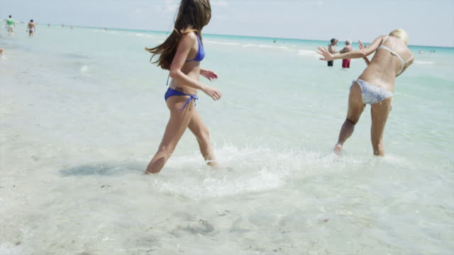 slo mo ws young women playing on beach/ south beach, miami, florida, usa - フロリダ州点の映像素材/bロール