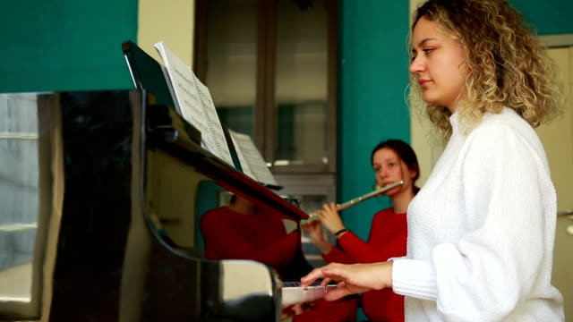 young women playing piano and flute - piano stock videos & royalty-free footage
