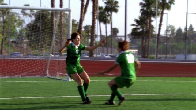 slo mo, ms, pan, young women playing soccer, scoring goal and cheering, biola university, la mirada, california, usa  - fan palm tree stock videos & royalty-free footage