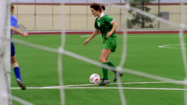 slo mo, ms, pan, young women playing soccer, view through goal post net, biola university, la mirada, california, usa  - nummer 4 bildbanksvideor och videomaterial från bakom kulisserna