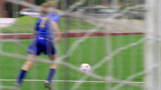slo mo, ms, pan, young women playing soccer, view through goal post net, biola university, la mirada, california, usa  - amateur stock-videos und b-roll-filmmaterial