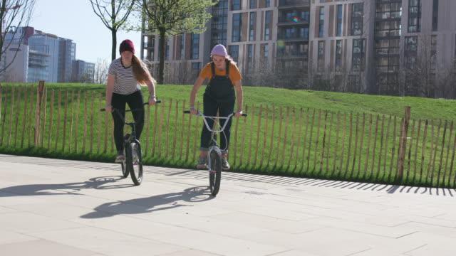 2人の若い女性がbmxバイクでフリースタイルを練習 - スタントバイク点の映像素材/bロール