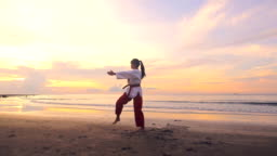 Young women Practising Martial Arts Outdoors On the beach at sunset, Slow motion