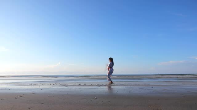 Junge Frauen üben Kampfkünste draußen am Strand, Long Exposure