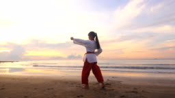 Young women Practising Martial Arts Outdoors On the beach