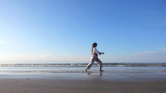 Junge Frauen üben Kampfkünste am Strand