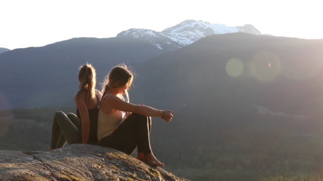 young women relax on mountain ledge, looking off - ärmelloses oberteil stock-videos und b-roll-filmmaterial