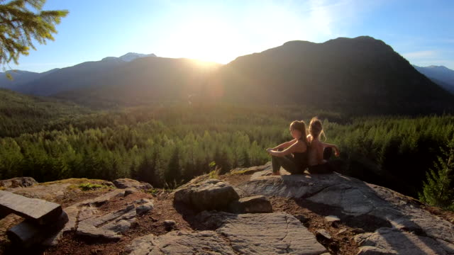 young women relax on rock summit, at edge of valley overlook - british columbia stock videos & royalty-free footage