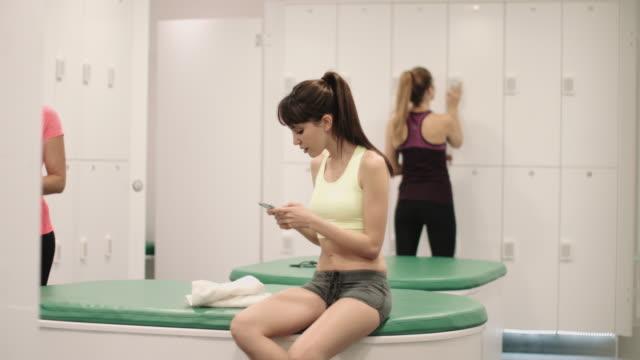 vídeos y material grabado en eventos de stock de young women relaxing in changing room after work out - sólo mujeres jóvenes