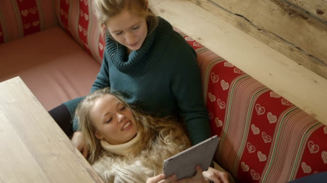 Young women relaxing on sofa and using digital tablet