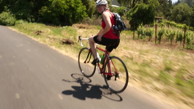 A young women riding her bicycle on a rural road in California Wine Country.