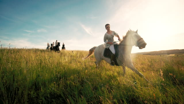 young women riding horses on grassy field - horseback riding stock videos & royalty-free footage