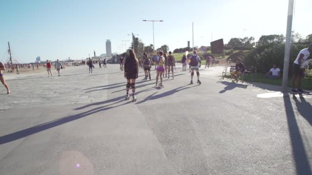 Young women roller skate through Barcelona promenade