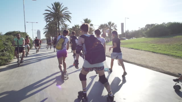 young women roller skate through barcelona promenade - 顕花植物点の映像素材/bロール