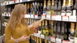 Young women scanning bar code with mobile phone on wine bottle