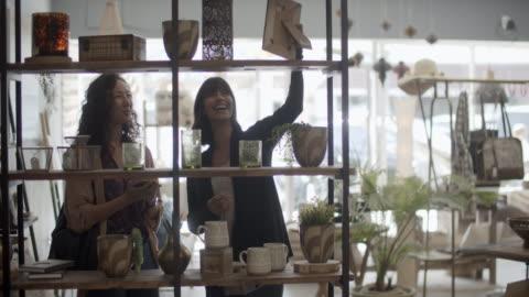 vídeos y material grabado en eventos de stock de young women shopping together in a sustainable store. - estante muebles
