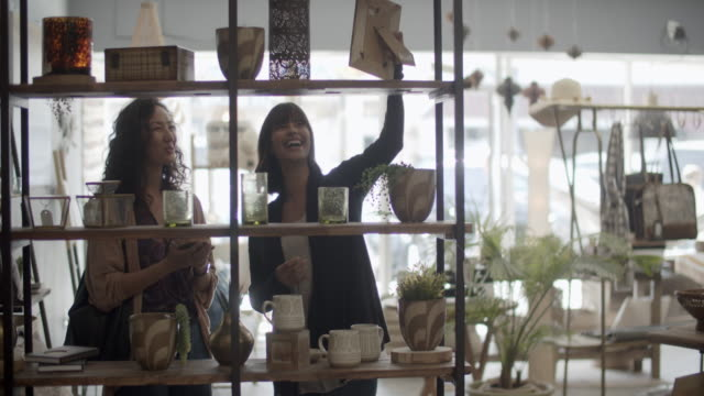 young women shopping together in a sustainable store. - customer stock videos & royalty-free footage