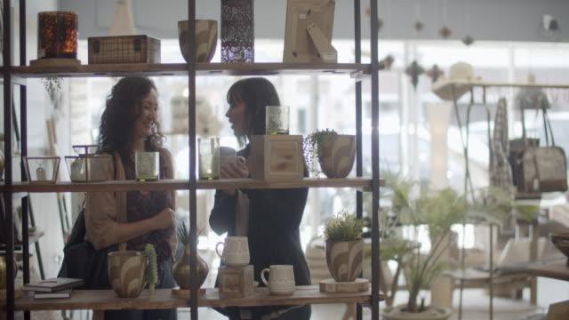 vidéos et rushes de young women shopping together in a sustainable store. - décoration de fête
