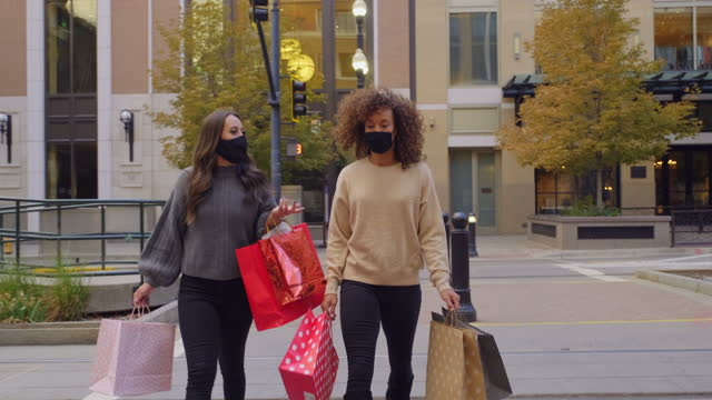 vídeos de stock e filmes b-roll de young women shopping with face mask on for protection - mercadoria
