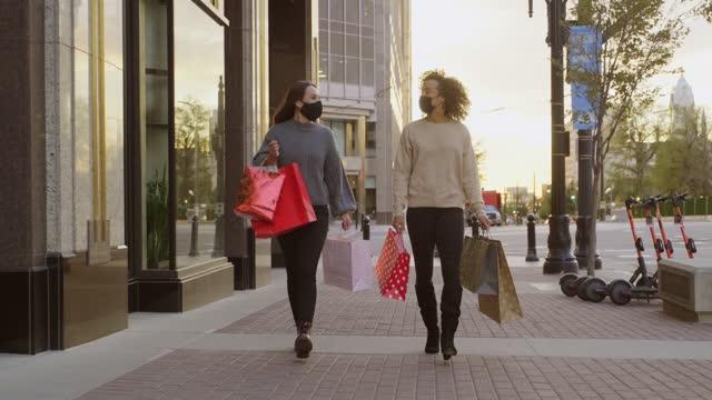 vídeos y material grabado en eventos de stock de young women shopping con máscara facial puesta para protección - amistad femenina