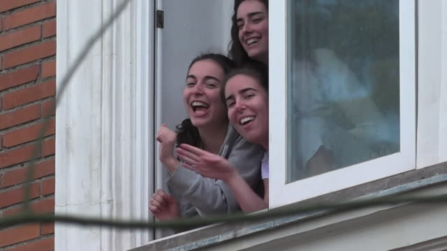 young women singing and applauding from window to hospital and health workers that are opposite, during lockdown in madrid due to coronavirus crisis - applauding stock videos & royalty-free footage