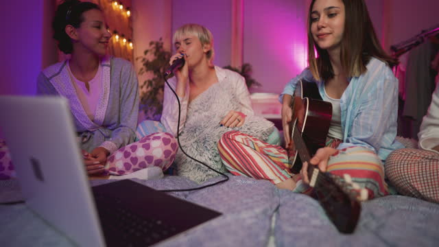 young women singing karaoke at a slumber party - slumber party stock videos & royalty-free footage