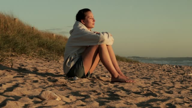 young women sitting breathing the air looking at the sunset on the beach in a calm moment - solo ragazze video stock e b–roll